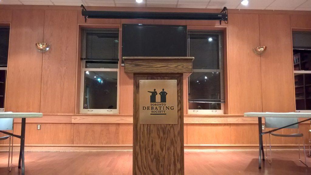 "Podium with ""Toronto Debating Society"" on front."
