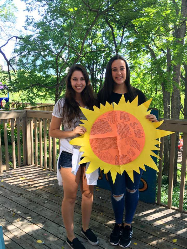 Taylor Laist and girl holding homemade paper sun with messages written in middle.