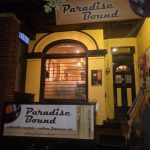 Yellow exterior of Paradise Brown with large jukebox-shaped window.