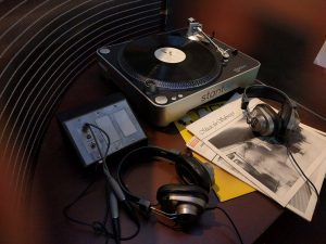 Table with record player, two sets of headphones and various record covers.
