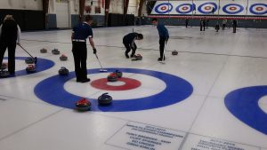 Ryerson curling team on ice with brooms and stones.and