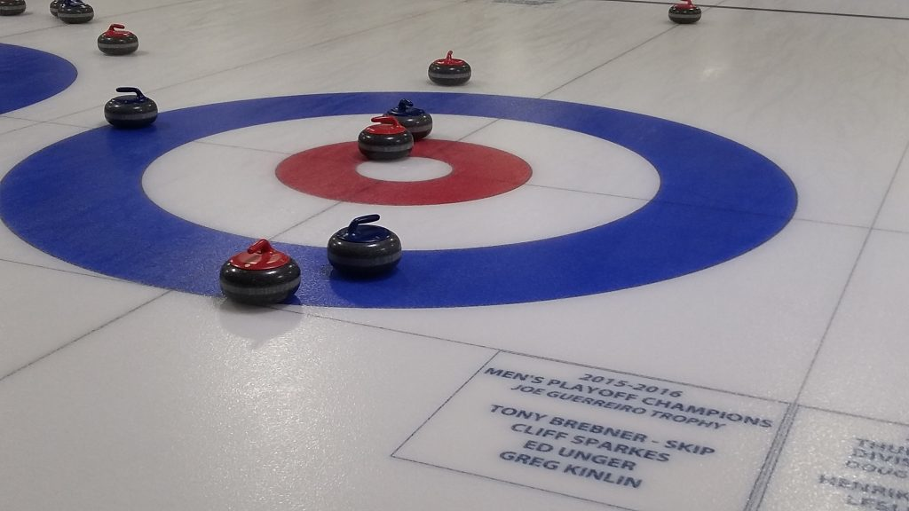 Curling rink with red and blue curling stones.