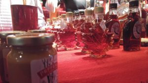 Bottles of syrup shaped like maple leaves sitting on red tablecloth.