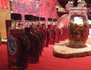 Bottles of maple syrup next to jar on red tablecloth.