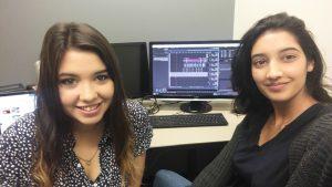 Reporters Natasha Hermann and Ammi Parmar in studio editing on computer.