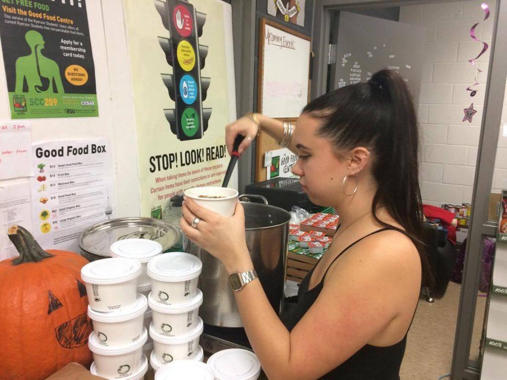 Ryerson student Claire Davis filling cups of lentil soup.