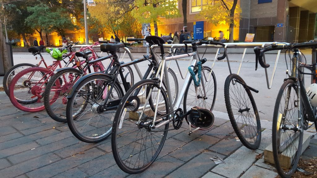 A series of bikes locked in a bike rack.