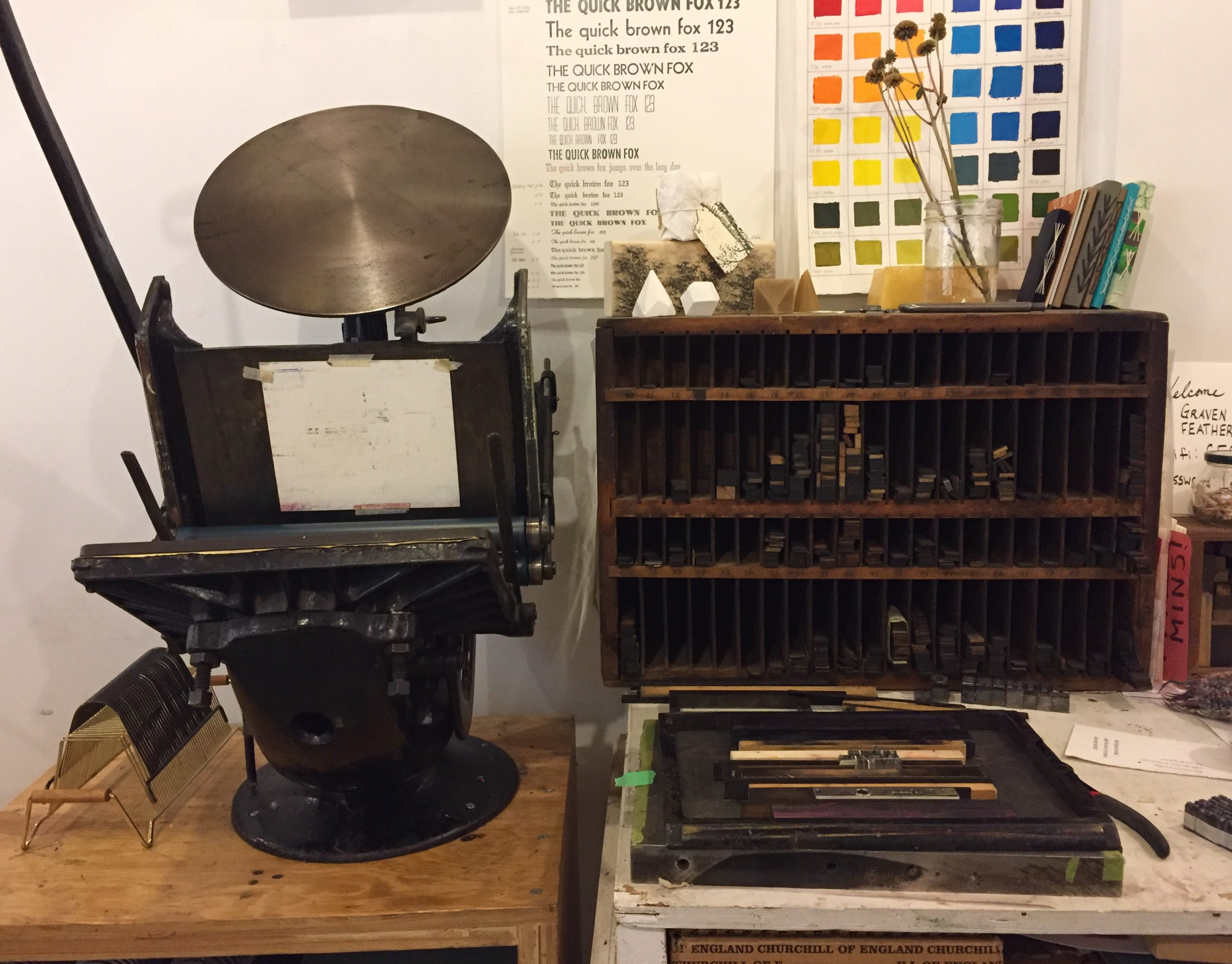 Letterpress machine sitting on desk with posters behind it.