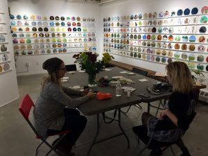Two women in workshop stitching surrounded by art