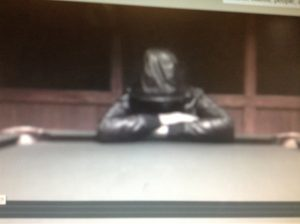 Blurred image of person in black jacket leaning cross armed and hooded leaning on pool table.
