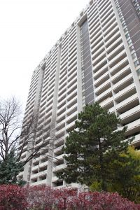 Large white apartment building surrounded by trees where Paige Smith lives.