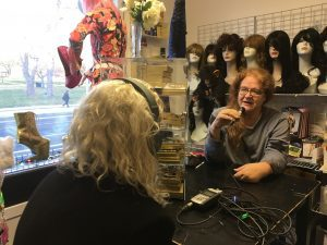 A woman interviews a second woman. Mannequin heads appear in the background showcasing a number of wigs.