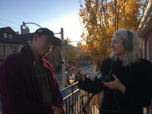 Woman wearing headphones holds a microphone towards a man as she interviews him outside on a balcony