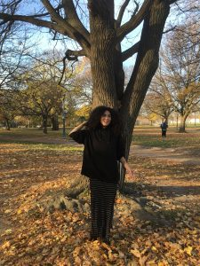 Toronto filmmaker Victoria Long standing in leaves in front of tree in Trinity Bellwoods park.