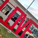 """Large red """"LOVE"""" sign in front of building."""