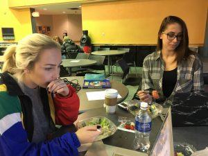 Ryerson students Alyssa Webster and Anyssa Close eating salads while looking at computers.