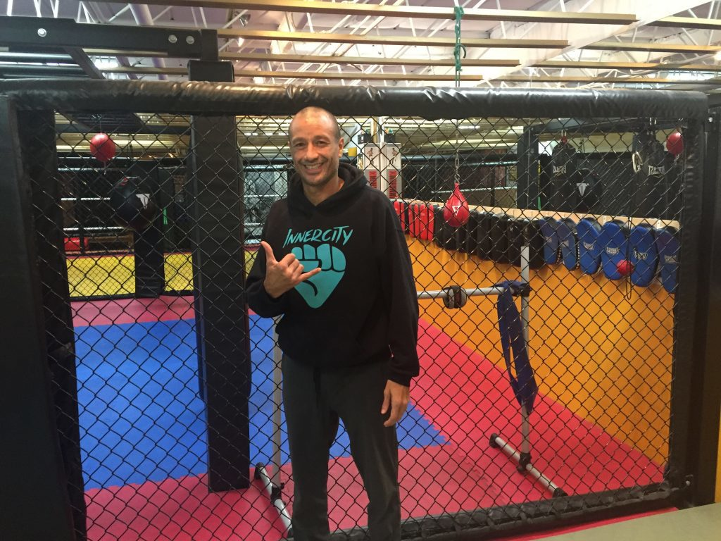"InnerCity MMA instructor Shah Franco standing in gym doing ""hang loose"" sign."