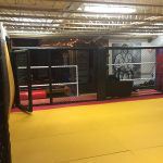 Interior of martial arts gym with yellow mats and black fencing surrounding it.