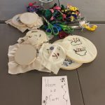 """Various cross-stitch pieces on display with scissors, string and paper reading """"bloom in a room""""."""