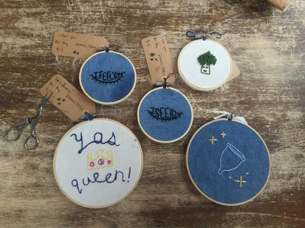 Five cross-stitch pieces on a wood table.