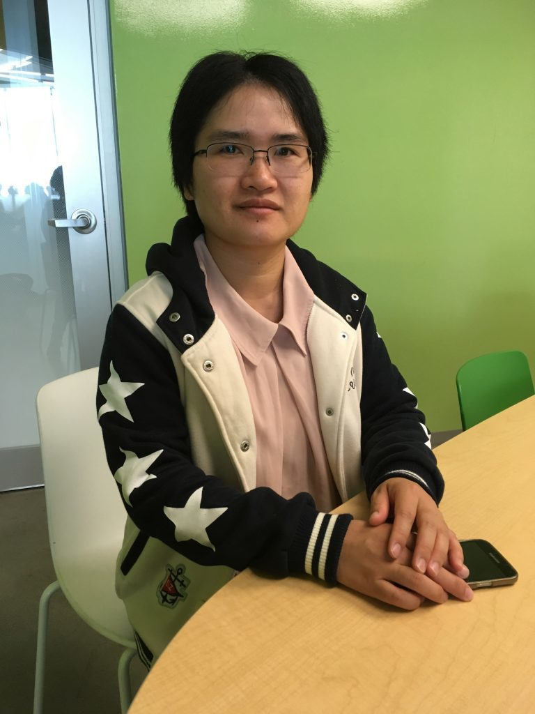 Juan Yu sitting in green study room in Ryerson Student Learning Centre.