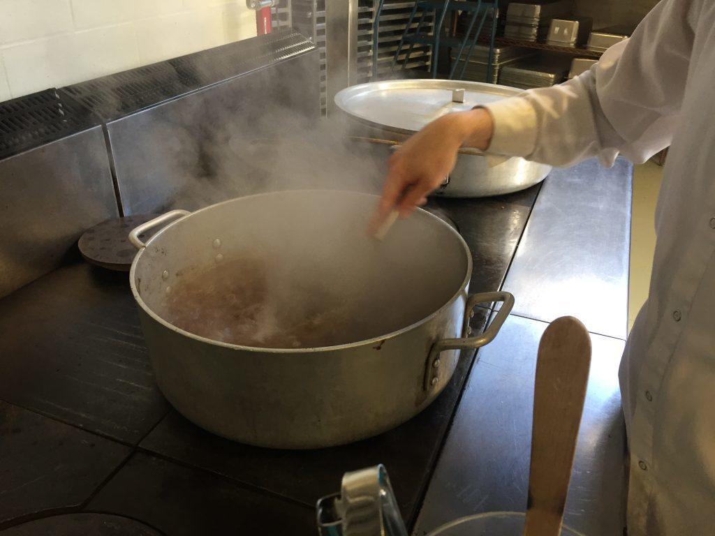 Volunteer cook stirring large pot of broth with whisk.