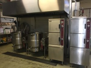 Industrial-style ovens and drums in kitchen.