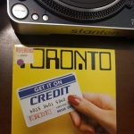 "Record of band titled ""Toronto"" with women's hand on cover holding card saying ""Get it on Credit""."