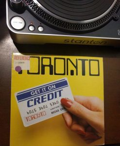 """Record of band titled """"Toronto"""" with women's hand on cover holding card saying """"Get it on Credit""""."""