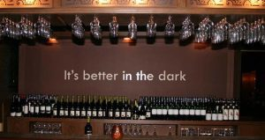 "Rows of wine bottles and glasses with writing on wall behind saying ""It's better in the dark"""