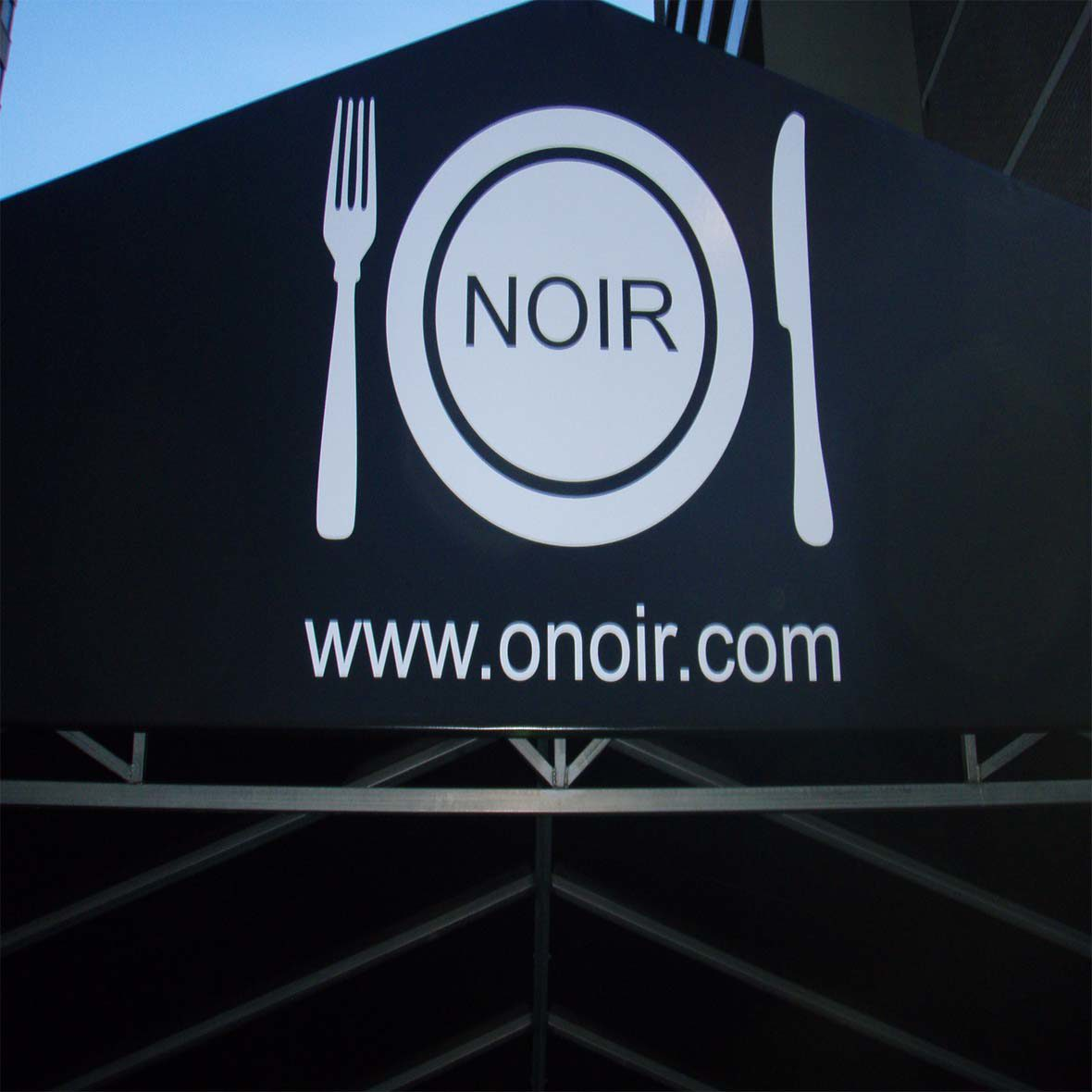 "Black triangular sign with fork, knife and dish that says ""ONOIR"" and www.onoir.com under."