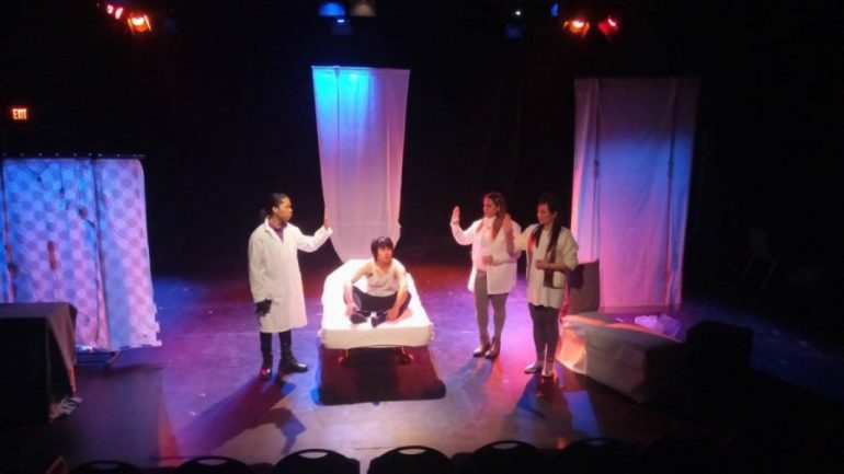 Four students on stage with white sheets hanging in background and man sitting on bed.
