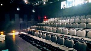 Rows of foldable black chairs in an empty theatre.