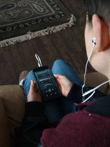 """Francesca with headphones in looking down at phone screen with """"Next to Normal"""" album cover."""