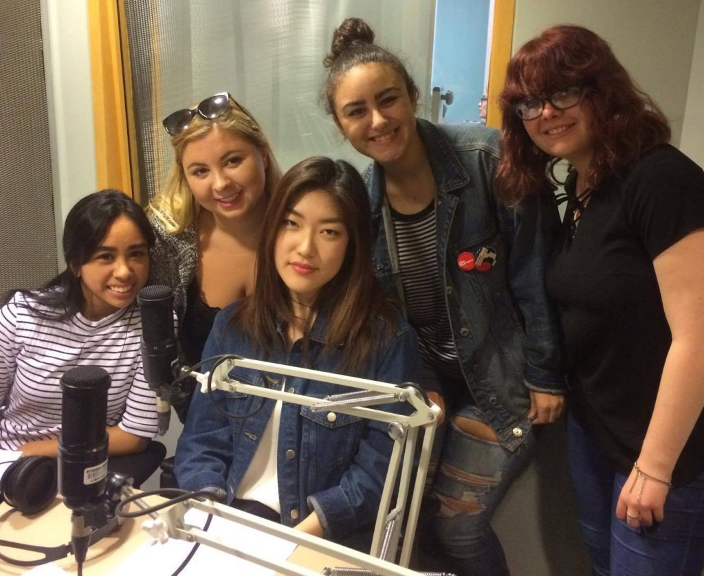Five women smiling in front of a microphone.