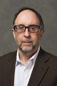 Portrait of Professor Doug Brugge against grey background.