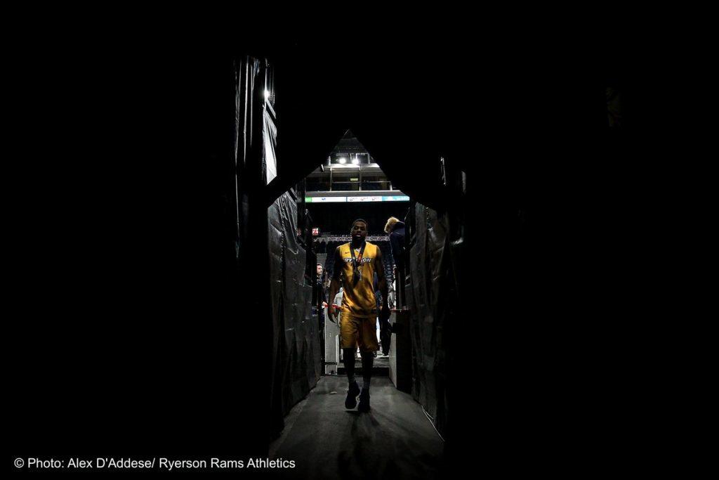 Athlete in yellow Ryerson jersey walking down dark hallway away from court.