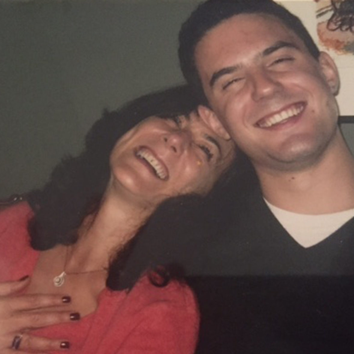 Woman with head on man's shoulder and both laughing