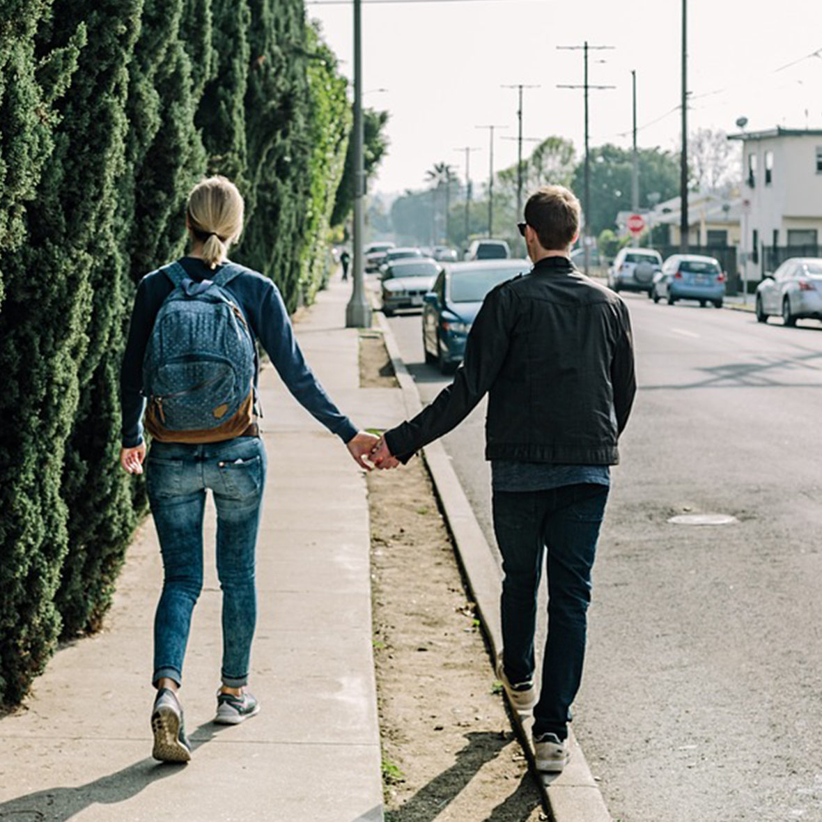 Woman with backpack on sidewalk and man on curb walking holding hands.