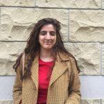 Portrait of Fatima Khawaja against brick wall.