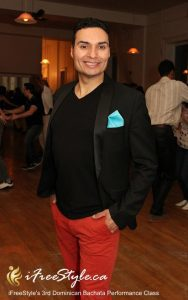 Portrait of man in black blazer and red pants standing on dance floor smiling with hands in pockets.