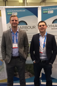 "Two men in suits and lanyards stand with their hands in pockets in front of ""SKYHARBOUR"" posters."