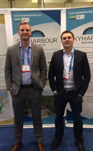 """Two men in suits and lanyards stand with their hands in pockets in front of """"SKYHARBOUR"""" posters."""