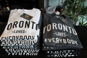 "Stacks of t-shirts in white and grey that say ""Toronto Loves Everybody""."