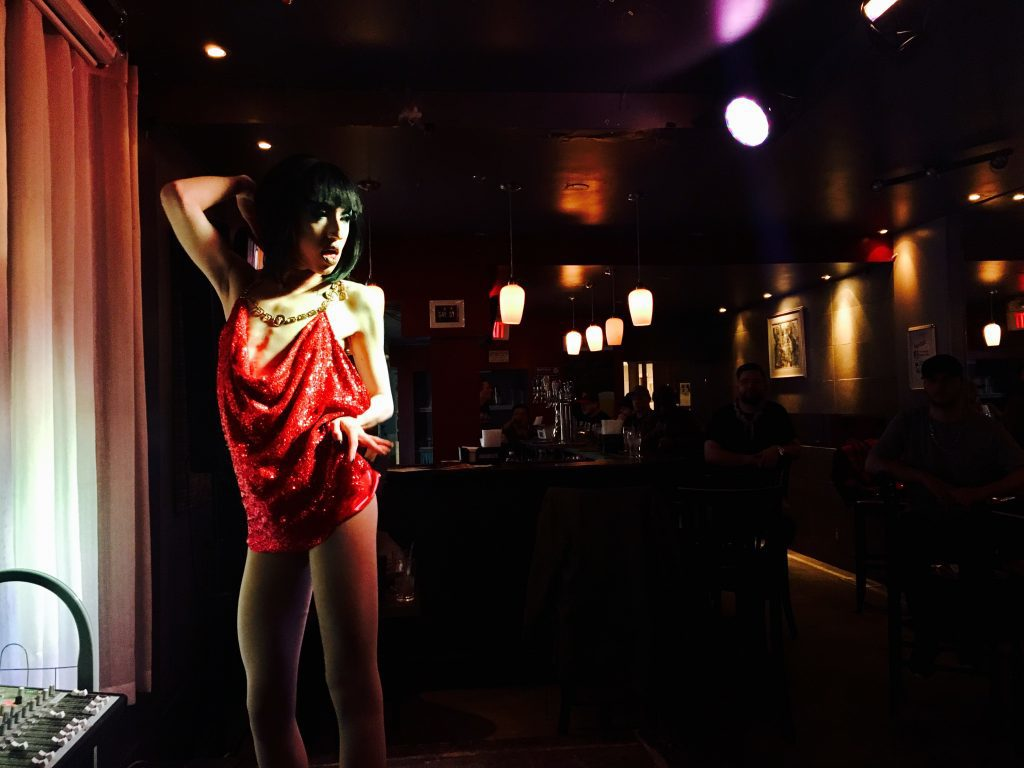 Woman in short red sequin dress dancing for restaurant patrons.