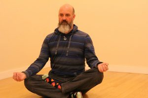 John Fortin sitting cross legged in the lotus position.