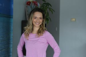 Portrait of yoga instructor Grabriela Nicole Doiu standing in pink yoga clothes in front of a shelf and plant.