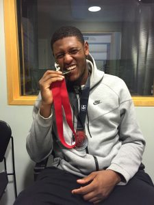 Juwon Grannum sitting with a medal around his neck biting a second medal.