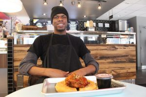 Cook Rashawan Farquason sitting in front of chicken and waffles with menu in background.
