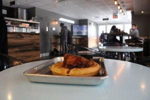 Side image of chicken and waffles with customers sitting in restaurant.